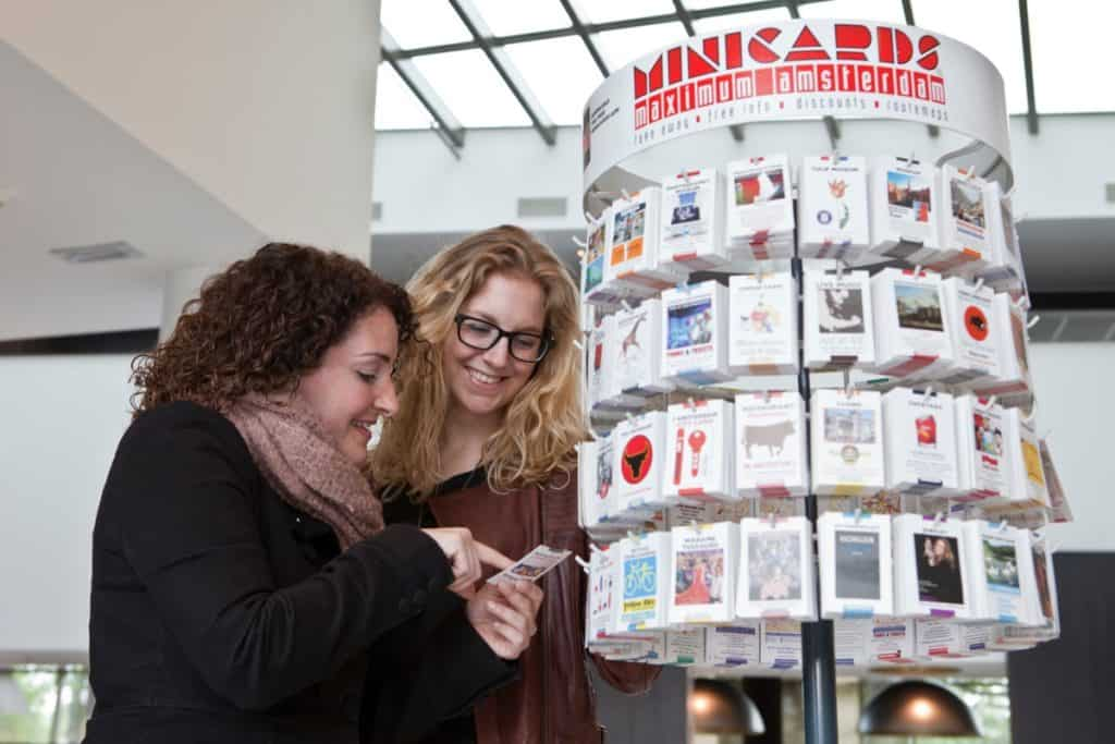 Tourists looking at Minicards at a display